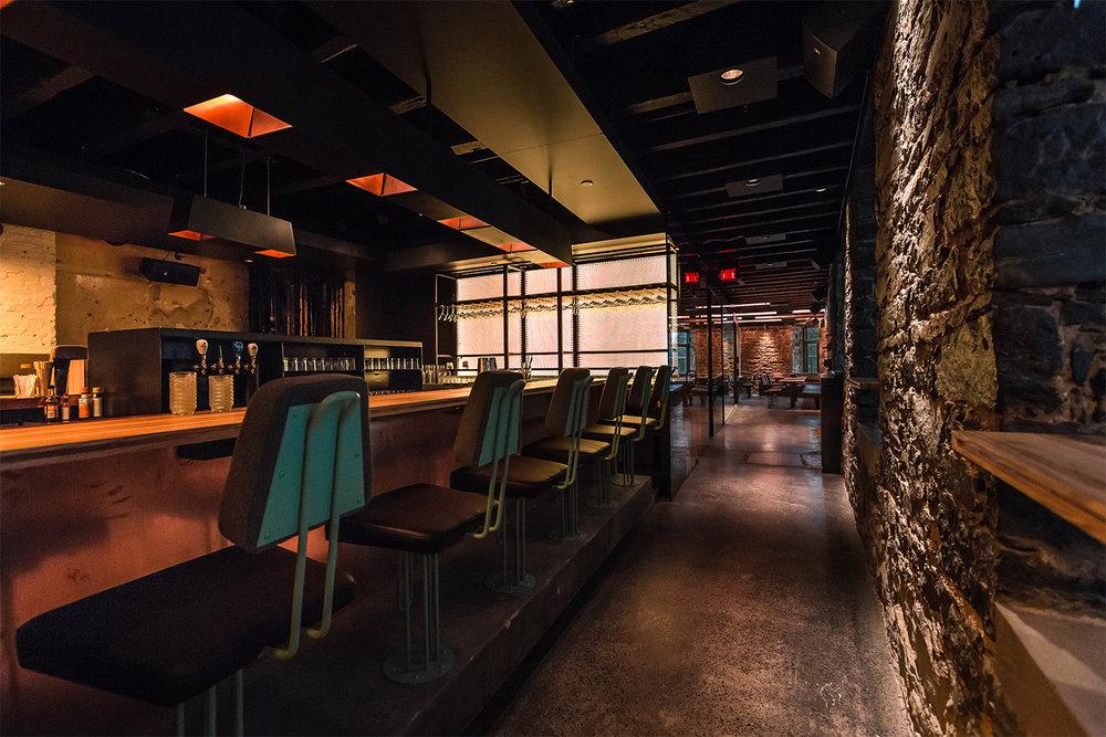 Vue du bar avec murs de pierres d'origines et plancher de béton poli. Le comptoir, fait de bois de hêtre, entouré de tabourets custom. L'arrière du bar rétro-éclairé mets en valeur les bouteilles
