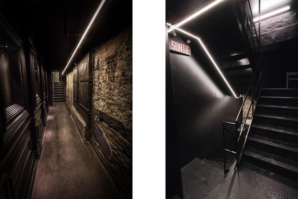 """Entrée """"secrète"""" menant au sous-sol, moderne et classique. Peinture noire lustrée sur murs moulurés en face du mur de pierres intégrant une porte d'origine. Un luminaire linéaire indique le chemin"""