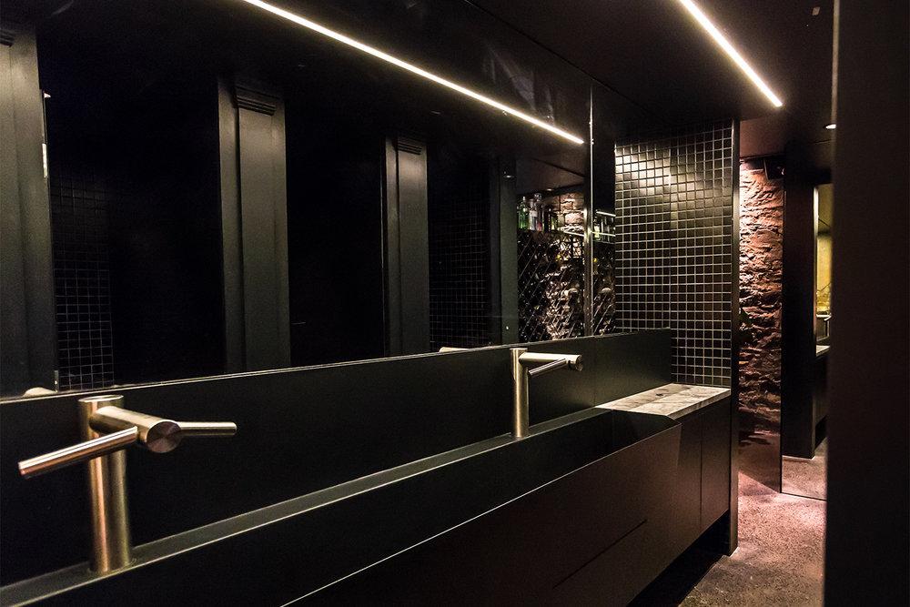 Salle de bain commerciale noir. Robinets automatiques installées sur le lavabo fait sur mesure en métal fini noir. Un grand miroir avec une section de mosaïque noire nous fait entrevoir les cabines