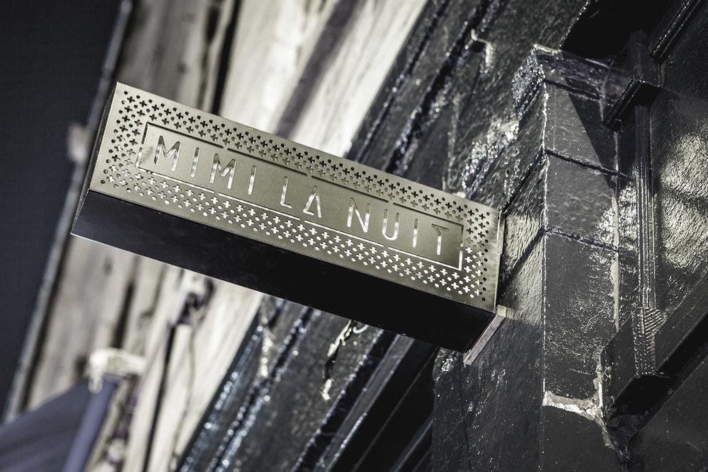 Enseigne de restaurant. Boîte lumineuse rectangulaire fait de métal noir perforé au laser. Motif minimaliste et moderne fait de points et de croix. Graphisme, typologie et branding intégré 360