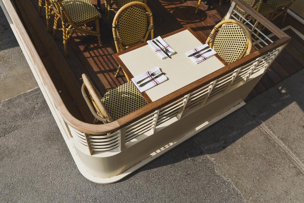 Vue détaillée de la terrasse du restaurant. Table avec moulure en bois et chaises bistro. Le plancher de la terrasse sont en Ipé et le reste de la structure en acier peint blanc cassé à la main.