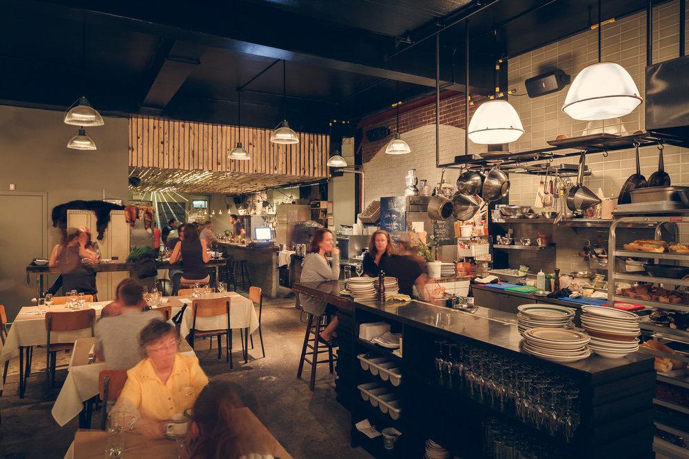 Salle à manger et vue de la cuisine. Le plafond recouvert de cèdre sans écorce laisse transparaître une douche lumière. Les murs d'origines et le plancher de béton donne un aspect industriel au lieu