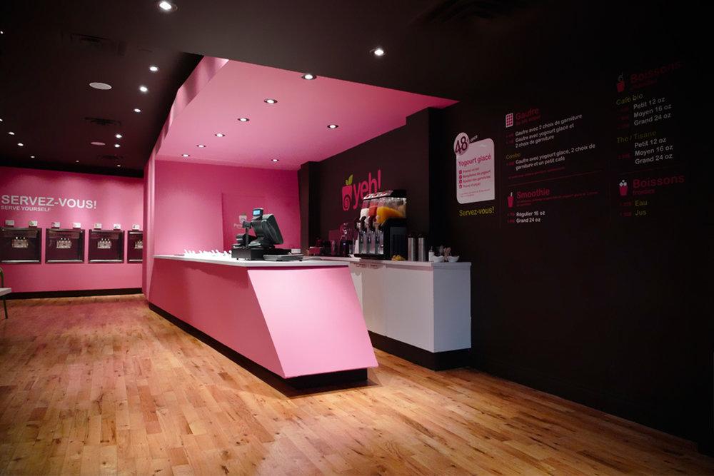 Vue de la boutique avec son plancher de bois franc. Le volume du comptoir caisse avec ses angles et sa couleur rose contraste sur les murs noirs. Nous apercevons au loin les distributrices encastrées