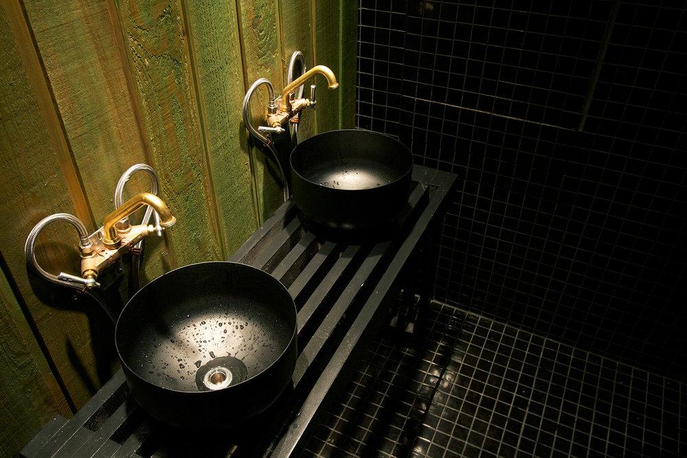 2 lavabos de salle de bain de type vasque déposés sur un comptoir de lattes de bois ajourés peint noir. La robinetterie murale brute avec arrivée d'eau visible. Mur et plancher finis mosaïque noir