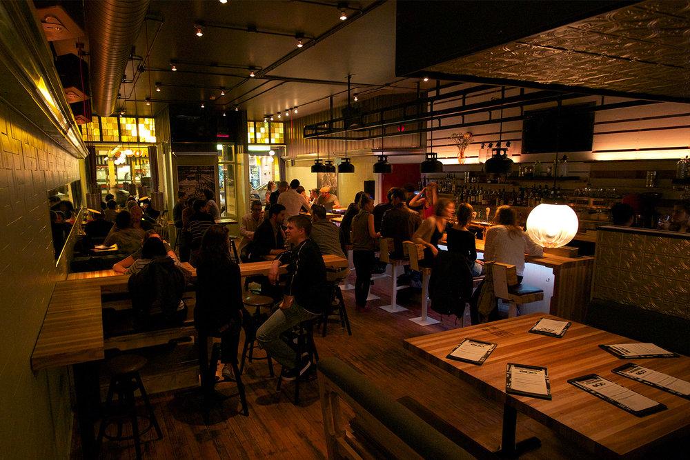 Vue de la salle à manger du restaurant avec clients. Tables et comptoir bar fait sur mesure imitant le bois de palette. Composition de 5 essences de bois : érable, frêne, merisier, hêtre, chêne.