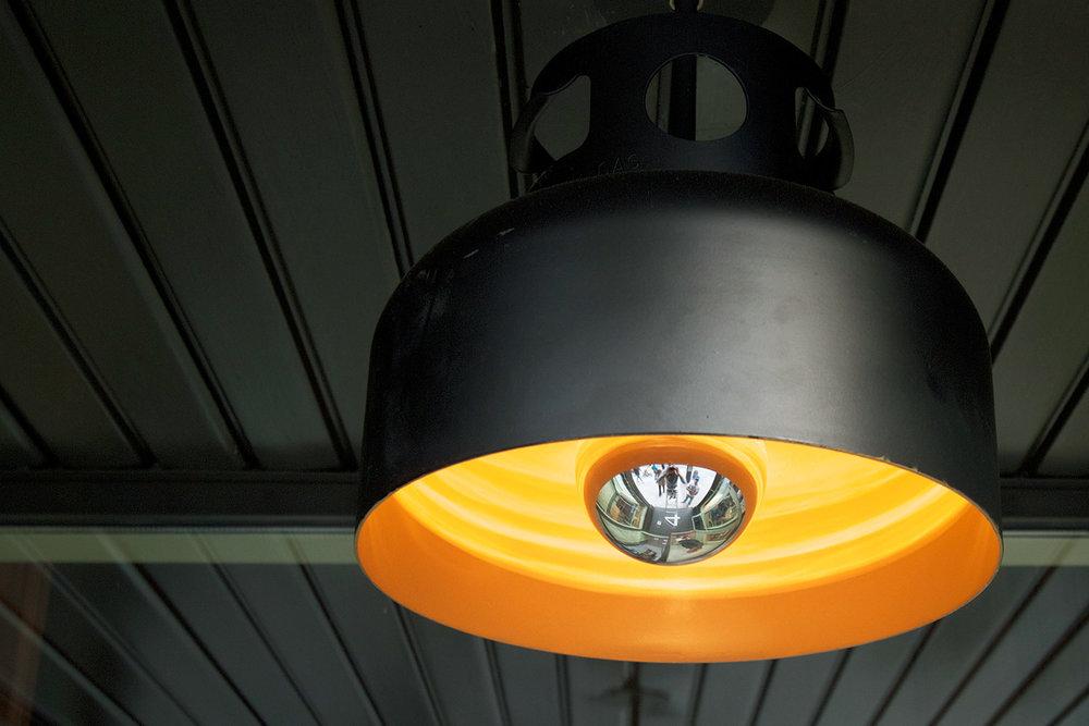 Détails des lampes au-dessus du bar. Luminaires fait sur mesure à partir d'une ancienne bonbonne de gaz. Fini extérieur noir mat et intérieur peint jaune. Une ampoule donne une lumière chaleureuse