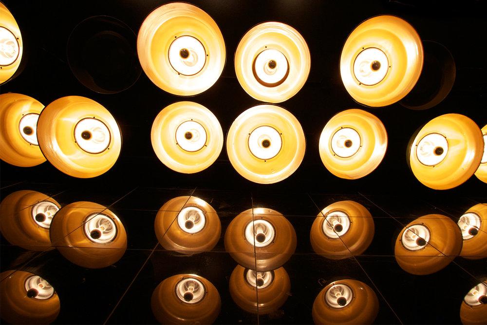 Vue en plongé du plafond menant aux toilettes. Lampes suspendues de type industrielles avec ampoules argentées installées à différentes hauteurs. Réflexion des luminaires dans un grand miroir