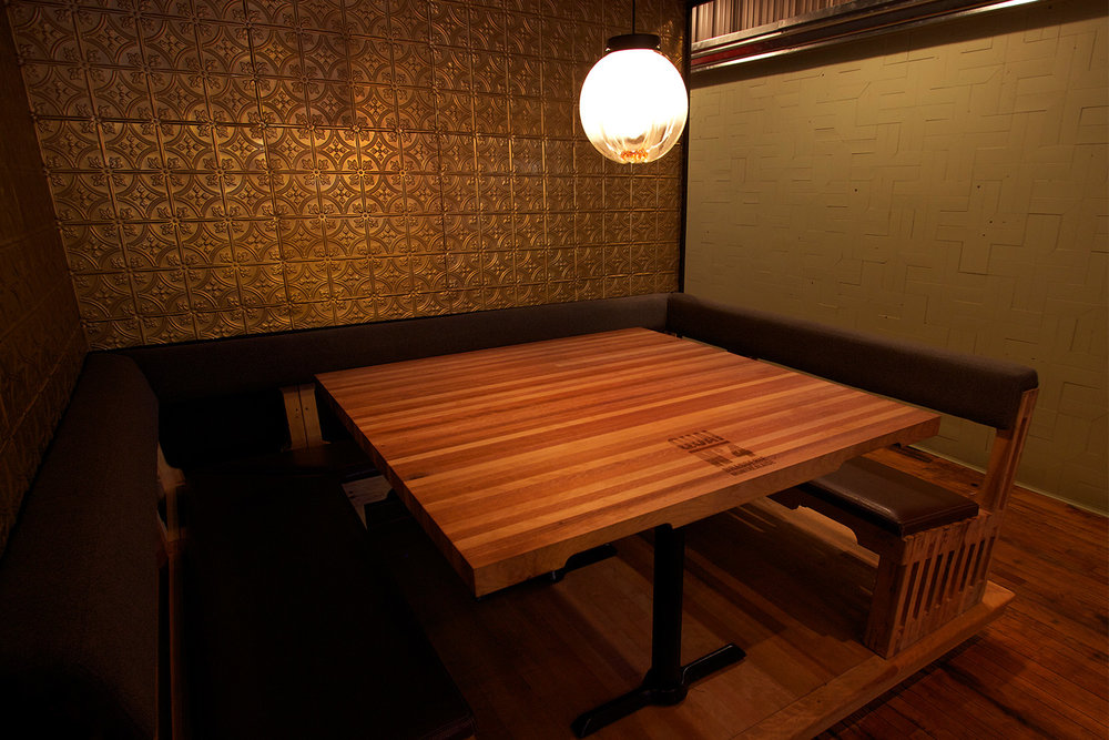 Vue d'une banquette en U fait de bois brut avec assise en cuir. Table à l'image d'une palette de transport. L'un des murs est recouvert d'anciennes tuiles de métal embossées avec motif de rosace