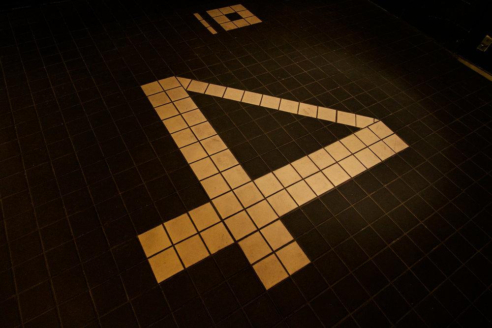"""Vue rapprochée du plancher de l'entrée du restaurant Quai n°4. Mosaïque 2""""x2""""noir mat avec insertion de carreaux blanc pour créer le logo"""