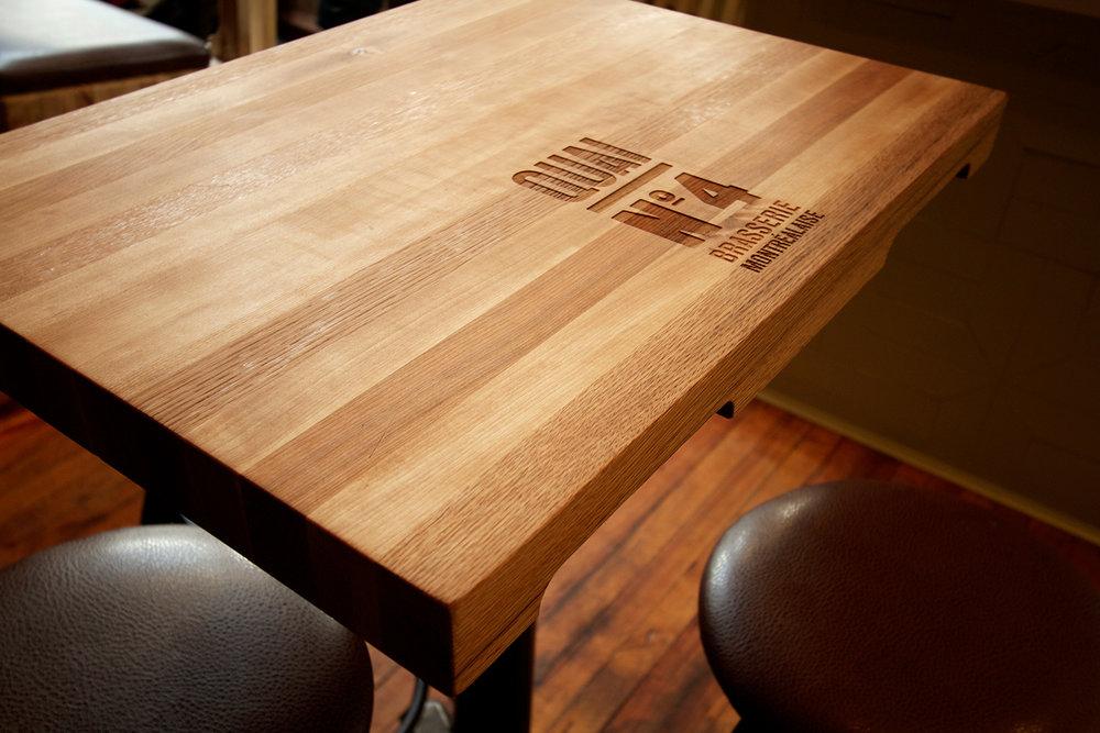 Table composée de 5 essences de bois différentes : érable, frêne, merisier, hêtre et, chêne. Gravure laser du nom du restaurant et encoches sur les chants rappelant les palettes de transport