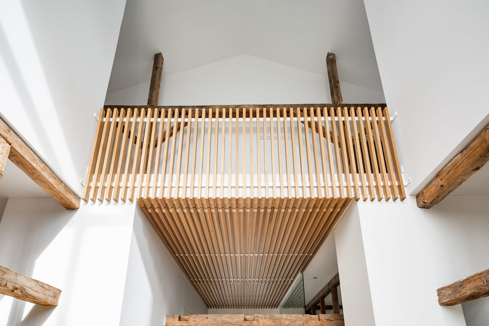 Garde-corps en lattes de chêne blanc se poursuivant au plafond de l'entrée. Ancienne structure de la grange en bois apparente. Plafond cathédrale en double hauteur
