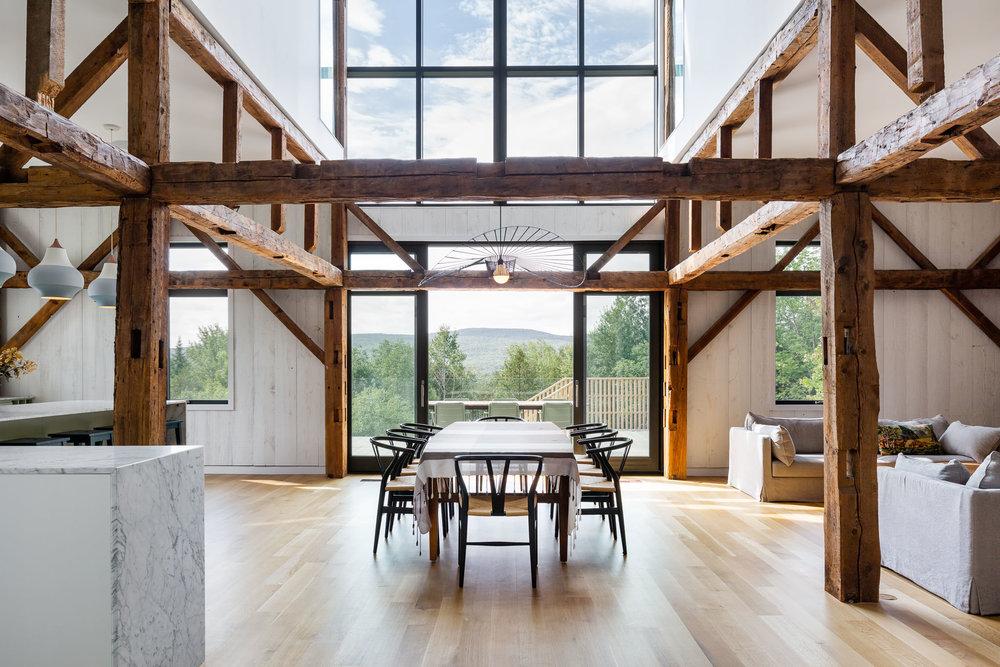 Salle à manger d'un chalet avec toit cathédrale et grande fenestration. Ancienne structure en bois apparente. Plancher de chêne blanc. Luminaire Vertigo au-dessus de la table, chaise Wishbone CH24