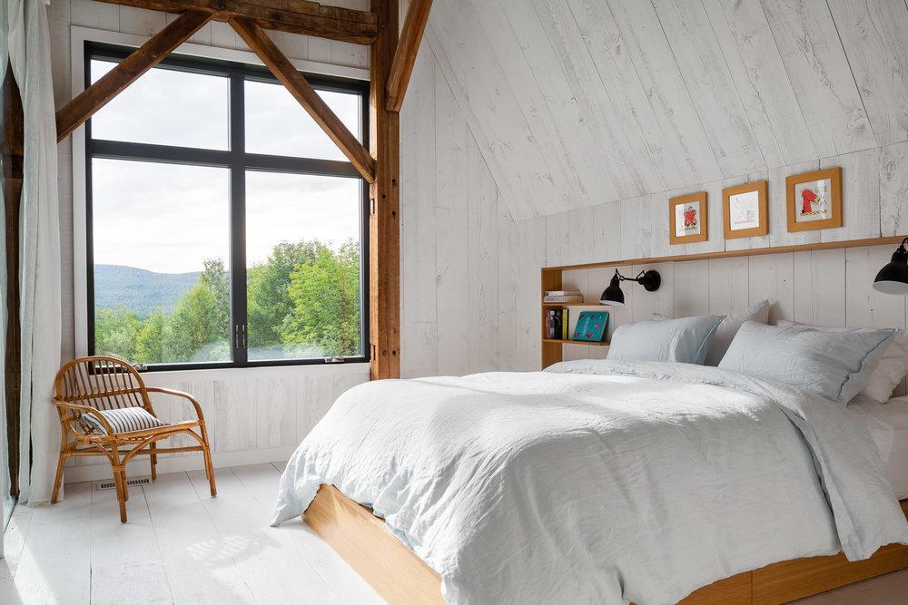 Mobilier de chambre fait sur mesure en chêne blanc. Lampes de chevet Gras. Mur de pruche et plancher fini en larges planches de cèdre peint blanc.