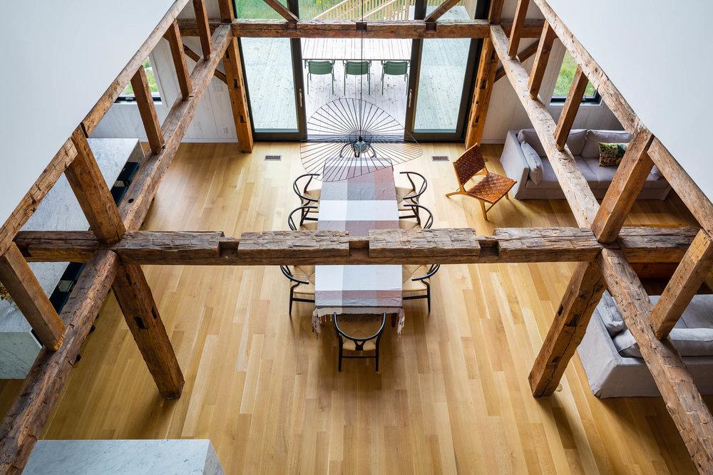 Salle à manger d'un chalet avec grande fenestration. Ancienne structure en bois apparente. Plancher de chêne blanc. Luminaire Vertigo au-dessus de la table, chaise Wishbone CH24