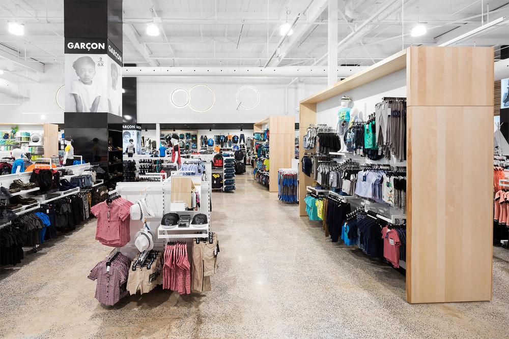 Boutique de vêtement avec plancher de béton poli. Étagère sur mesure en bois avec crémaillère blanche. Colonne signalétique pleine hauteur noir pour identifier les différentes sections