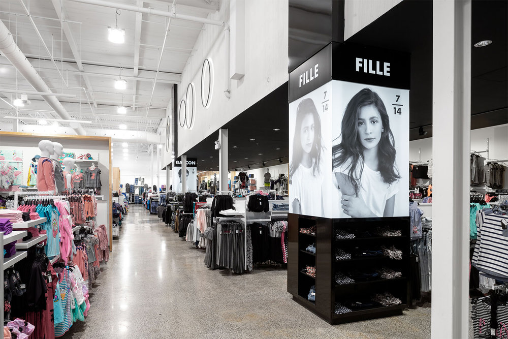Boutique de vêtement avec plancher de béton poli. Colonne signalétique pleine hauteur noir. Plafond abaissé et peint en noir dans la zone adolescent