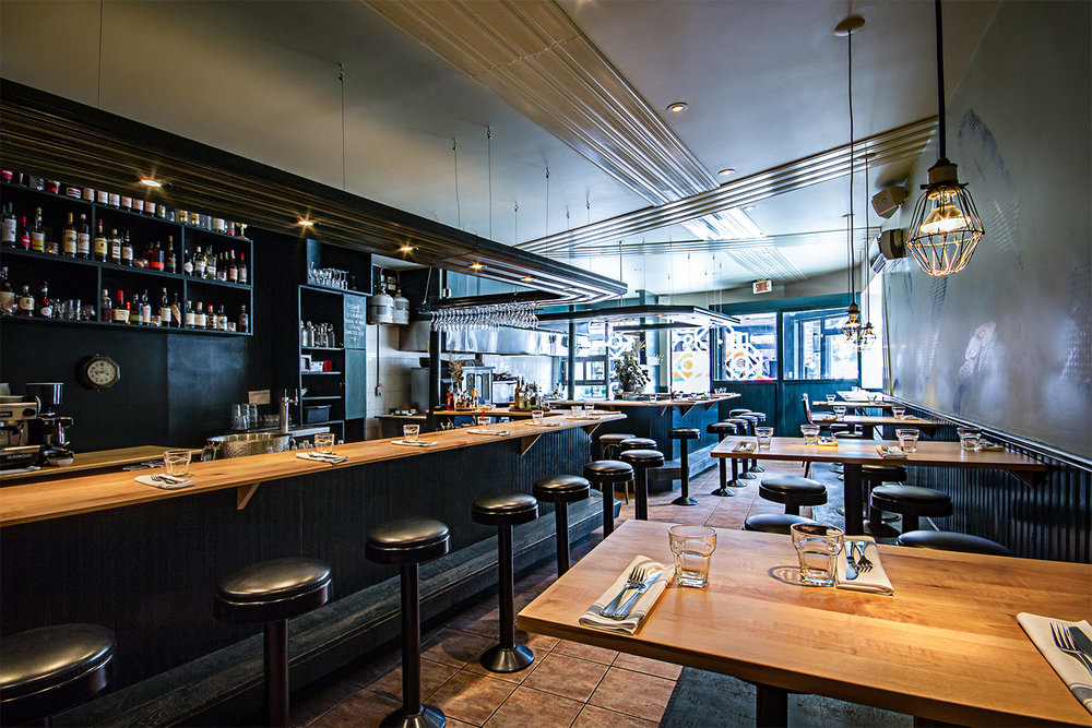 Vue intérieure du restaurant avec son bar fini bois fait en 2 sections et une partie de la salle à manger. Moulures décoratives finies lustrées suspendues au-dessus du comptoir avec éclairage intégré