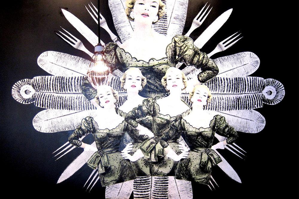 Motif type mandala composé de personnages féminin en robe à pois avec fourchettes et couteaux agrémenté de quelques plumes