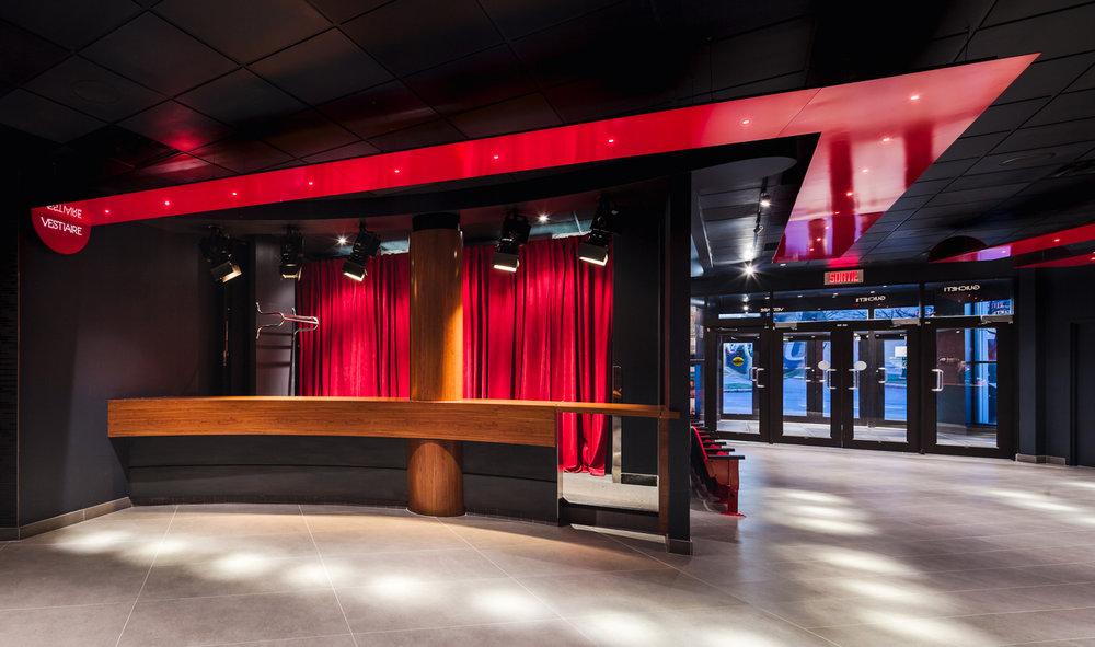Vestiaire d'une salle de spectacle avec rideaux de velour rouge en arrière plan. Comptoir et colonne recouvert de noyer. Signalétique en métal peint rouge suspendue avec inscription lumineuse