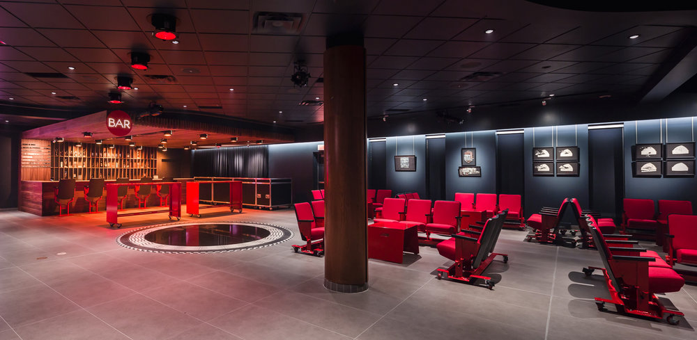 Bar fabriqué en noyer noir et luminaires scéniques récupérés. Section lounge avec bancs rouge sur roulettes fait d'anciens sièges de salle de spectacle récupérés. Caissons transformés en bars mobiles