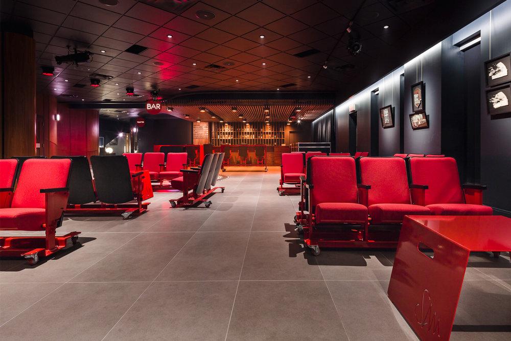 Section lounge avec bancs rouge sur roulettes fait d'anciens sièges de salle de spectacle récupérés. Petites tables rouges faites sur mesure empilables en pliage d'acier avec découpe laser du logo et poignées intégrés