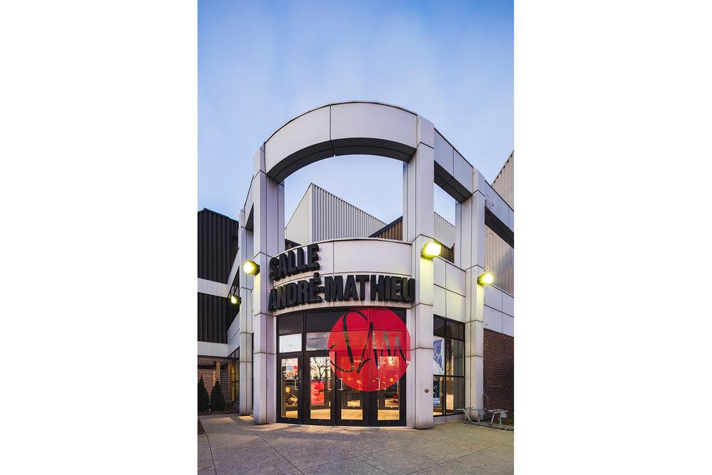 Vue de la façade principale de la salle André-Mathieu à Laval. Intégration du nouveau logo dans la vitrine. Pastille rouge avec lettrage en négatif.