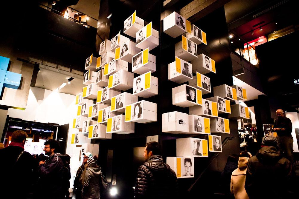 Installation de boites de cartons blanches avec impression d'une photo et description de l'artiste. Montage des boites sur 2 murs dans l'entrée de la cinémathèque