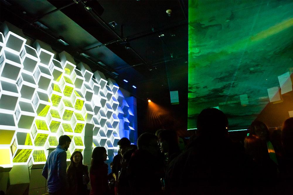 Installation d'un mur de boites de carton en angle. Projection multimédia (mapping) sur les arrêtes des cubes. Vidéo projection jaune et blanc