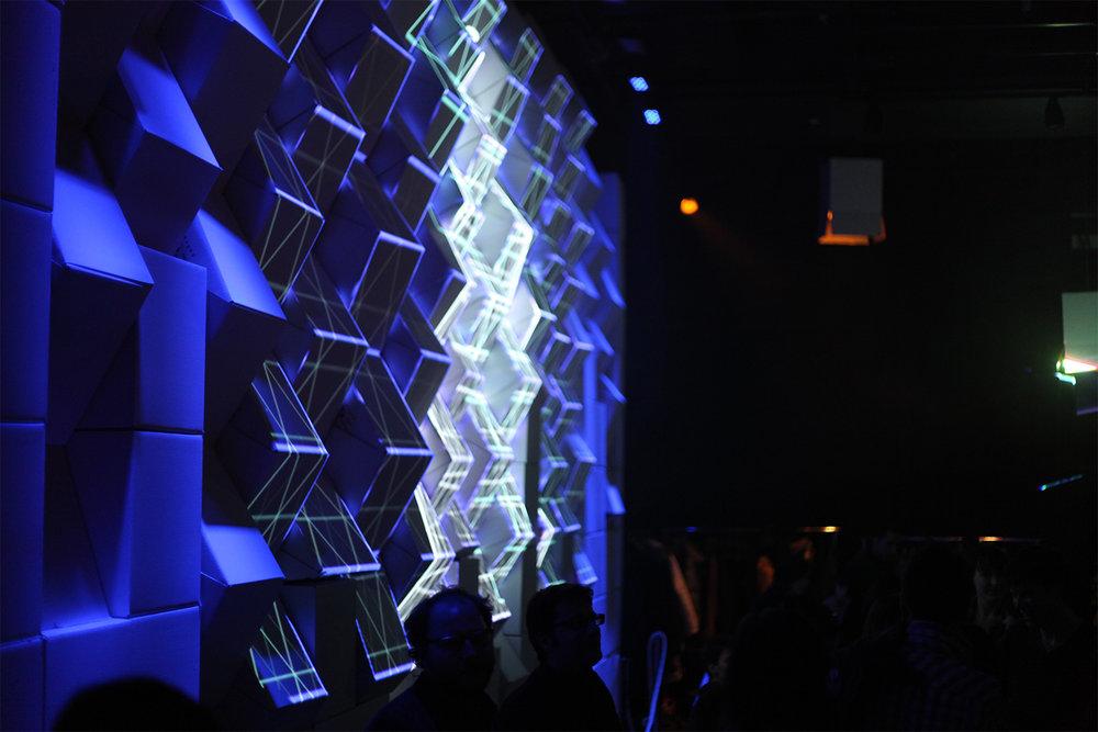 Installation d'un mur de boites de carton en angle. Projection multimédia (mapping) sur les arrêtes des cubes. Vidéo projection bleu et blanc