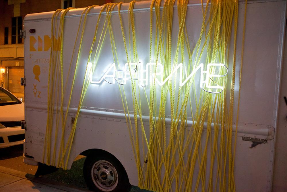 Camion La Firme utilisé pour les RIDM décoré de nombreuses cordes jaunes. Logo fluorescent installé sur le côté extérieur du véhicule.