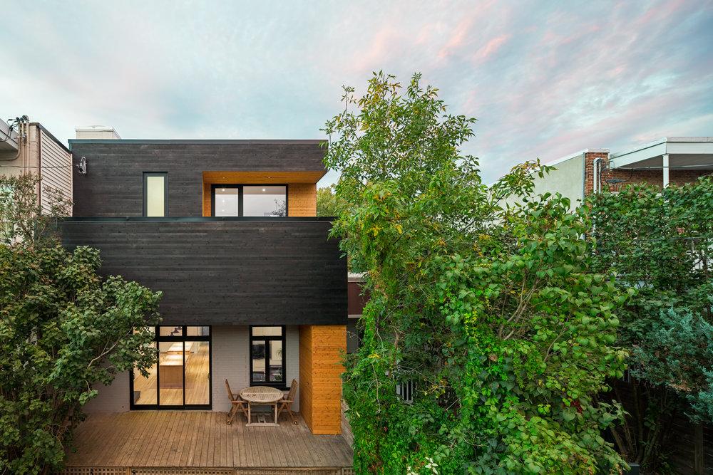 """Agrandissement d'une maison unifamiliale de type """"shoe box"""". Ajout d'une mezzanine. Revêtement extérieur en planches de bois carbonisées de type Shou-sugi-ban et autres section en cèdre blanc."""