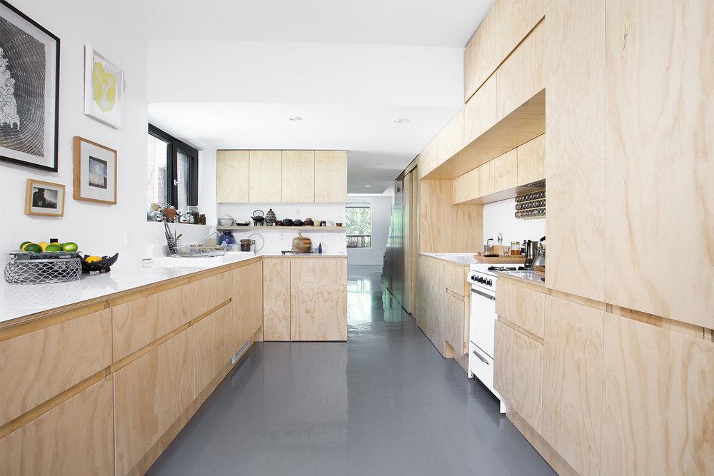 Rénovation complète d'une cuisine. Caissons sur mesure fait par ébéniste en contreplaqué merisier russe. Cuisinière au gaz avec comptoir blanc lustré. Plancher d'époxy gris lustré