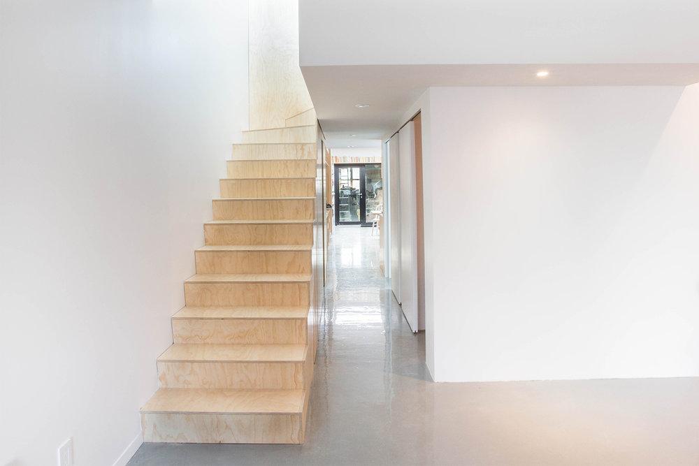 Vue de l'escalier en contreplaqué merisier russe dans un espace minimaliste. Portes coulissantes et plancher d'époxy gris lustré