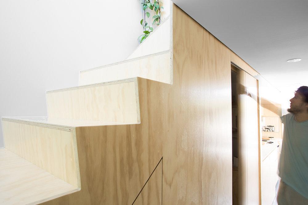 Création d'un nouvel escalier en contreplaqué merisier russe. Rangement dissimulé sous les marches avec porte coulissante.