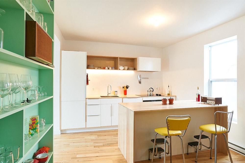 Rénovation d'un duplex. Aménagement de la cuisine. Caissons préfabriqués et comptoir de bois sur mesure. Bibliothèque intégrée turquoise