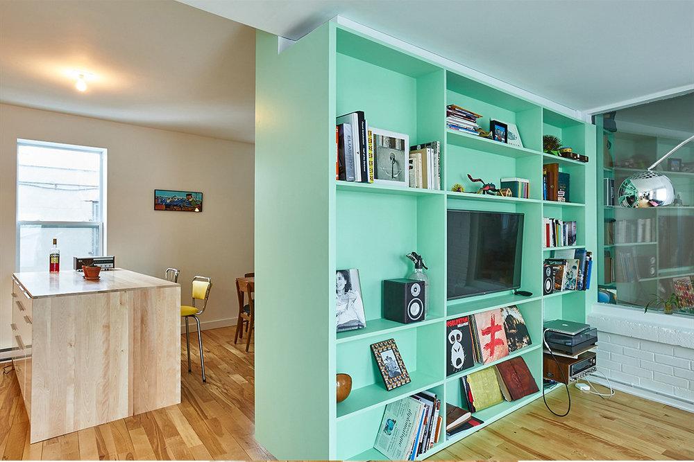Bibliothèque intégrée turquoise. Rangement pour disque vinyles et télévision. Mobilier sur mesure. Plancher de merisier.