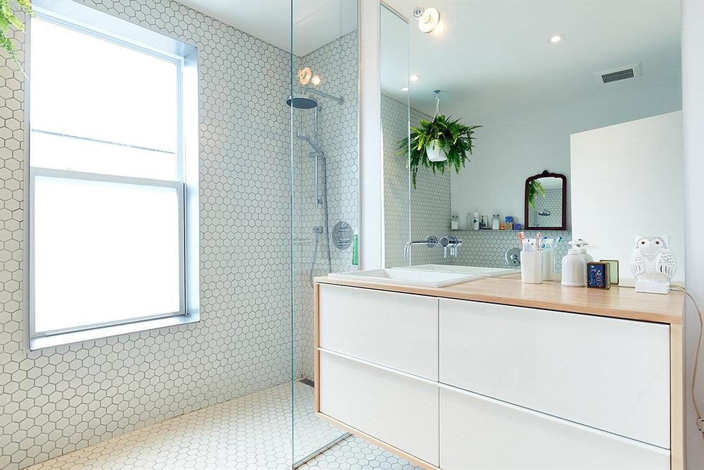 Rénovation de salle de bain. Plancher et mur de mosaïque blanche octogonale. Miroir sur mesure pleine hauteur avec meuble vanité blanc. Le comptoir de bois merisier entour le meuble suspendu au mur