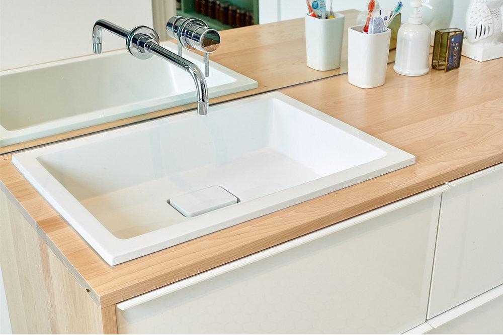 Meuble de salle de avec comptoir de bois et lavabo en surface. Lavabo épuré avec cache drain et robinetterie murale sur miroir.