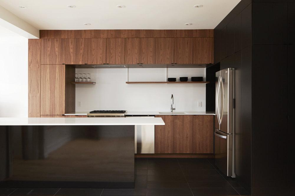 Rénovation d'une cuisine résidentielle. Garde-manger et armoires hautes fini noir. Autre section de cabinets sur mesure en noyer noir et îlot recouvert de feuille d'acier fini peinture électrostatique