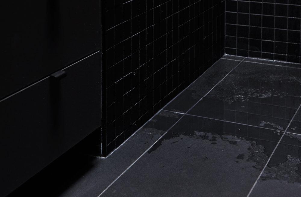 Vue du coin de la salle de bain. Plancher de céramique noir avec mosaïque 2x2 noir au mur. Meuble lavabo noir.