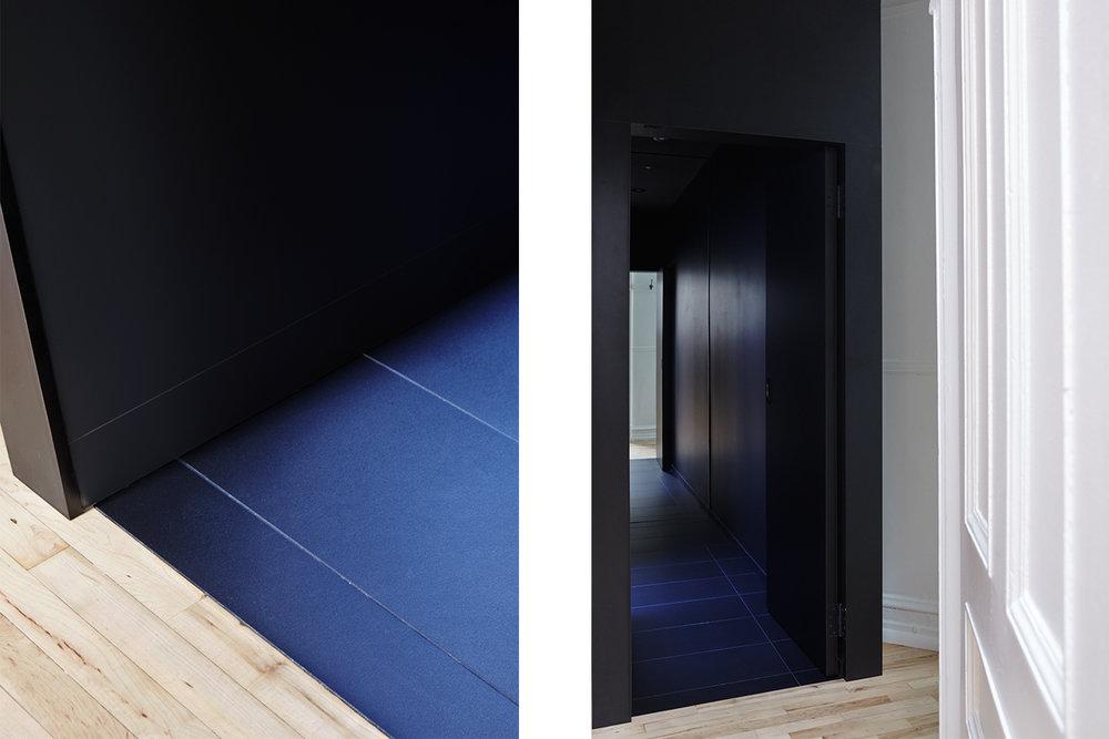 Détail de la jonction des différents finis de plancher: bois et céramique. Porte d'entrée de la salle de bain avec grand miroir au fond. Volume noir indépendant