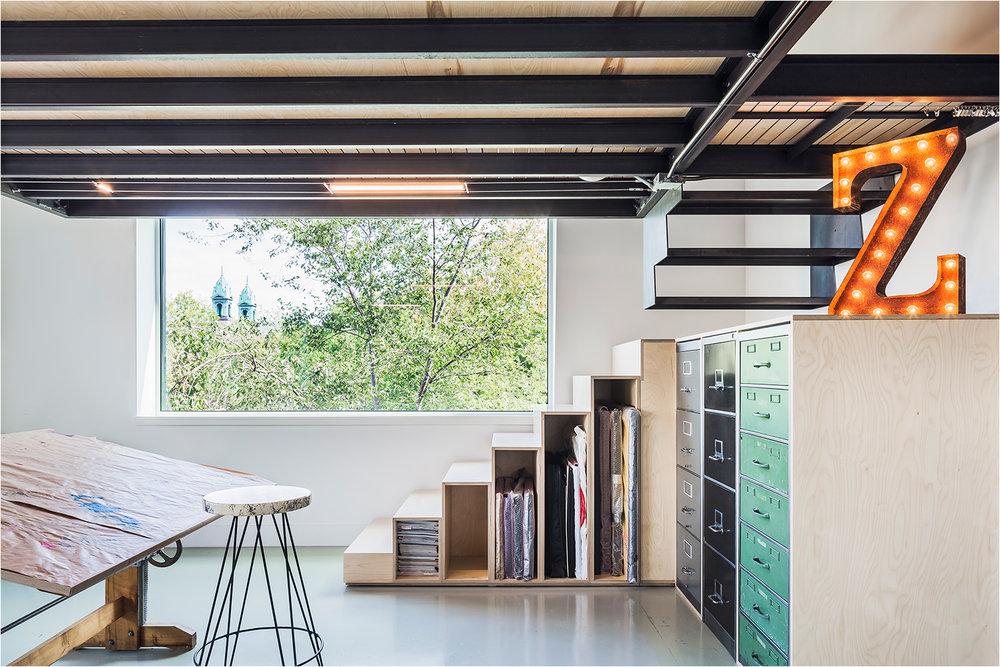 Atelier d'artiste situé dans un loft du quartier Mile-Ex. Ajout d'une mezzanine pour y aménager un bureau. Rangement custom sous escalier de contreplaqué. Plancher de béton poli. Lettre lumineuse