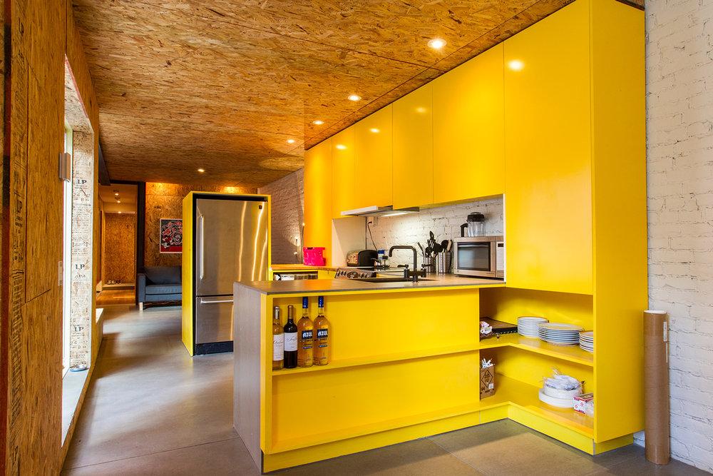 Rénovation d'un appartement. Mur de briques peint blanc. Nouvelle cuisine sur mesure jaune. Plancher de béton. Plafond et murs finis en panneaux d'osb