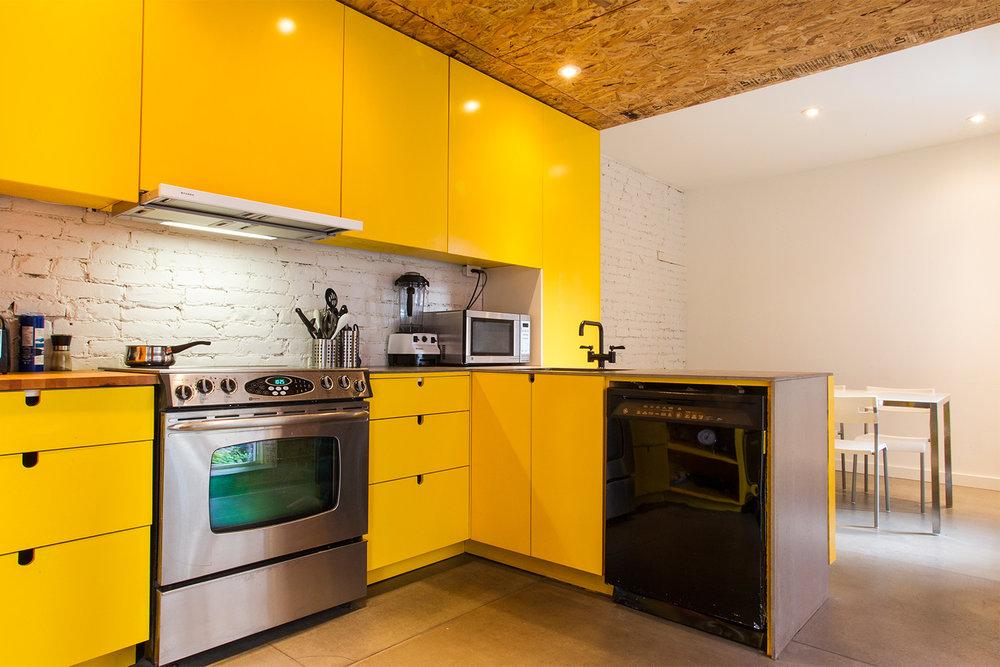 Rénovation d'un appartement. Mur de briques peint blanc. Nouvelle cuisine sur mesure avec caissons jaune. Plancher de béton. Plafond fait de panneaux de copeaux (OSB)