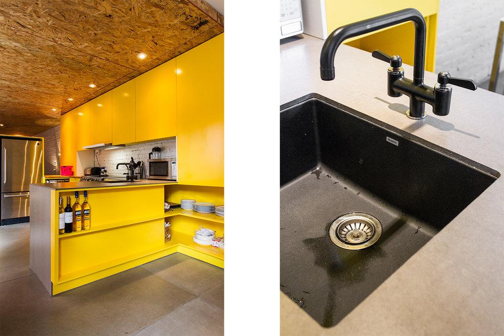 Mur de briques peint blanc. Cuisine sur mesure jaune. Plancher de béton. Plafond fini avec panneaux d'osb. Comptoir fait de panneaux de fibro-ciment. Évier en silgranit noir.