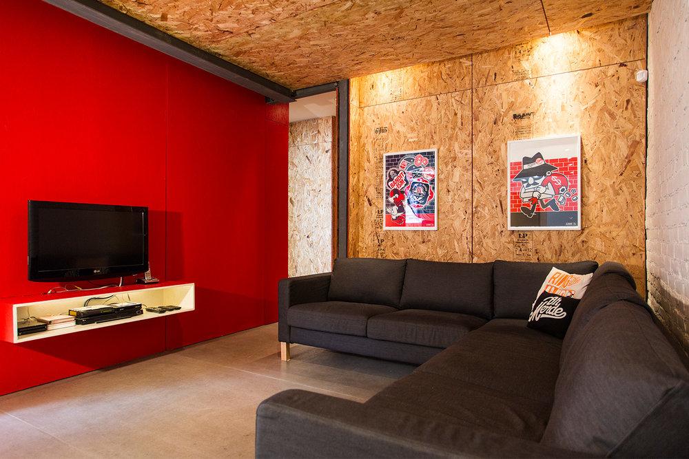 Rénovation d'un appartement sur le plateau. Mur de briques peint blanc. Plancher de béton. Plafond et murs fait de panneaux de copeaux (OSB). Mur accent rouge. Affiches 123 klan