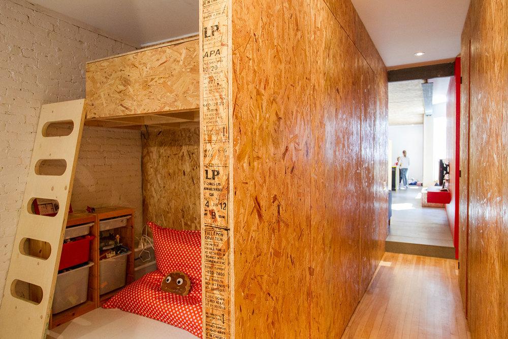 Rénovation d'un appartement sur le plateau. Chambre d'enfant avec lit mezzanine. Cloisons et division fait de panneaux de copeaux (OSB). Mur de briques peint blanc