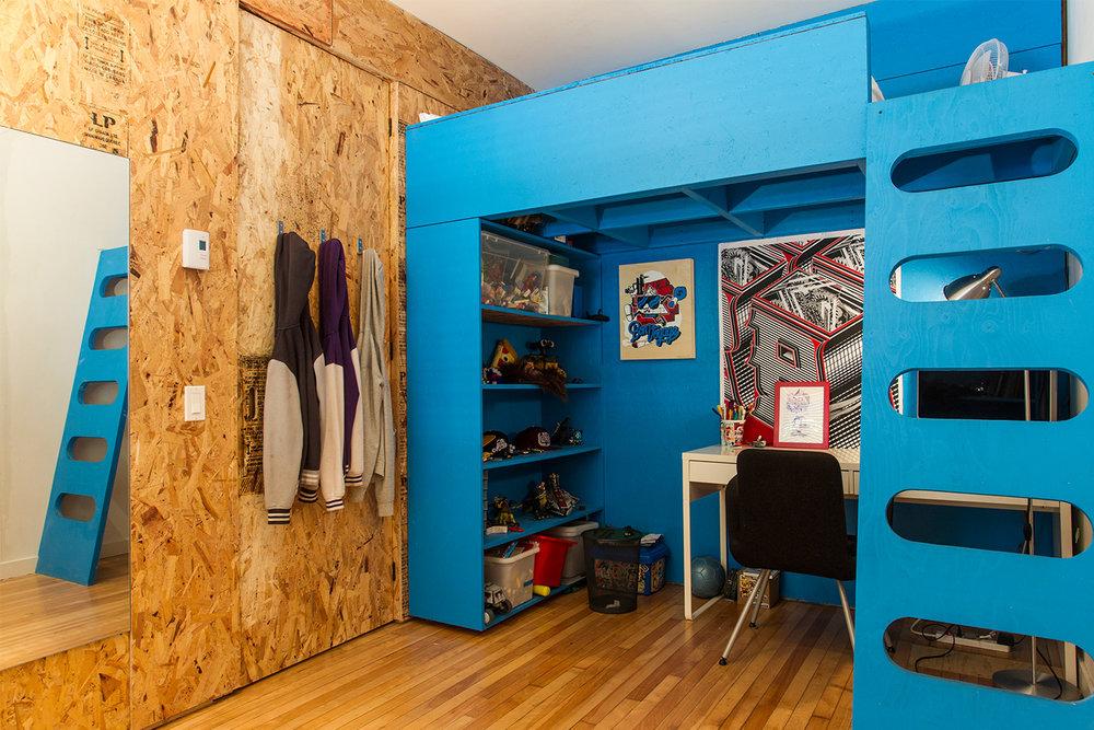 Rénovation d'un appartement sur le plateau. Chambre d'enfant avec lit mezzanine sur mesure peint bleu. Bureau sous le lit. Échelle custom. Murs fait de panneaux de copeaux (OSB)