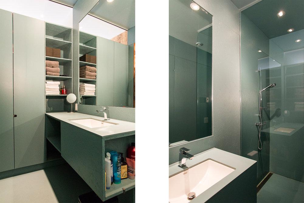 Rénovation d'une salle de bain monochrome vert-gris. Armoire de rangement sur mesure avec étagère ouverte. Vue sur la douche avec drain linéaire et paroie vitrée pleine hauteur.
