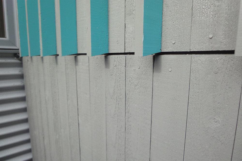 Façade extérieur, parement de bois gris. Board and batten moderne. Baguettes peintes bleu turquoise sur une face